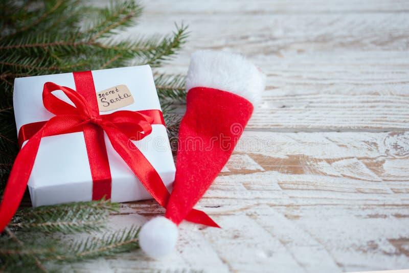 Boîtier blanc ou présent de Noël avec le ruban rouge pour Santa secrète avec le chapeau de Santa sur la table en bois photo stock