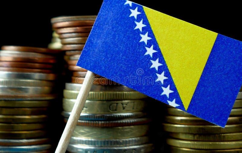 Bośnia i Herzegovina chorągwiany falowanie z stertą pieniądze monety zdjęcie stock