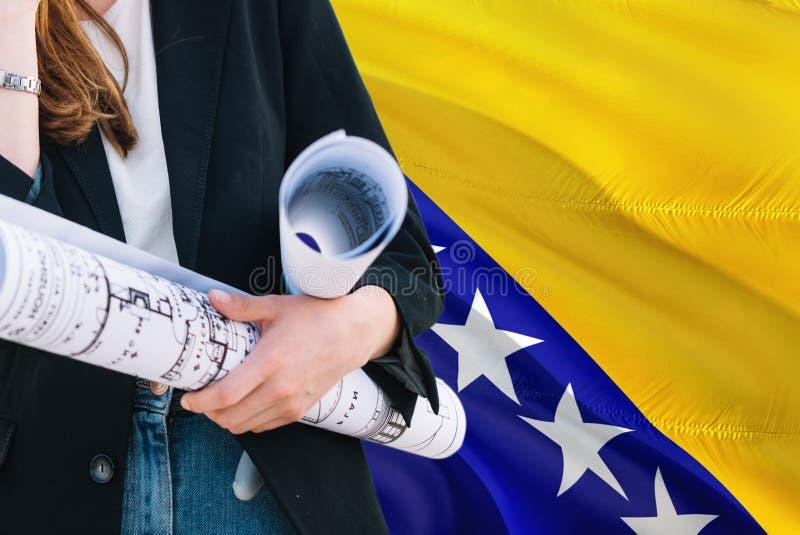 Bośniacki architekt kobiety mienia projekt przeciw Bośnia, Herzegovina falowania flagi tłu - Budowy i architektury poj?cie obrazy stock