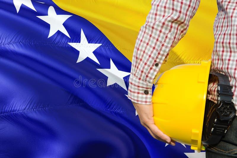 Bośniacki inżynier trzyma żółtego zbawczego hełm z machać Bośnia, Herzegovina chorągwianego tło - Budowy i budynku poj?cie zdjęcia royalty free