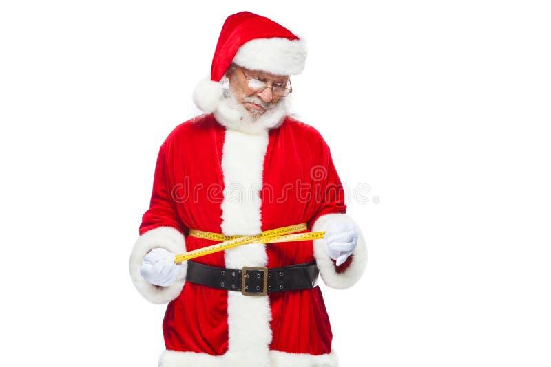 Boże Narodzenia Święty Mikołaj jest pomiarowym talią z taśmą Pojęcie ciężar strata, zdrowy łasowanie Odizolowywający na bielu obraz stock