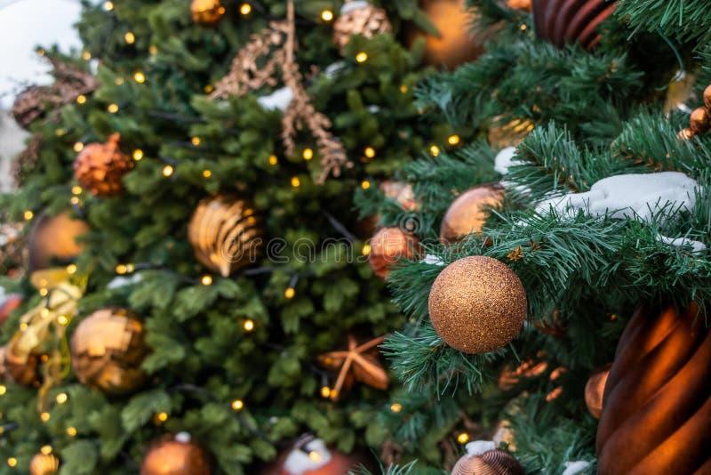 Boże Narodzenia bawją się na zielonym drzewie z śniegiem Złota piłka w górę, Bożenarodzeniowe zabawki i błyszczące pi obrazy stock