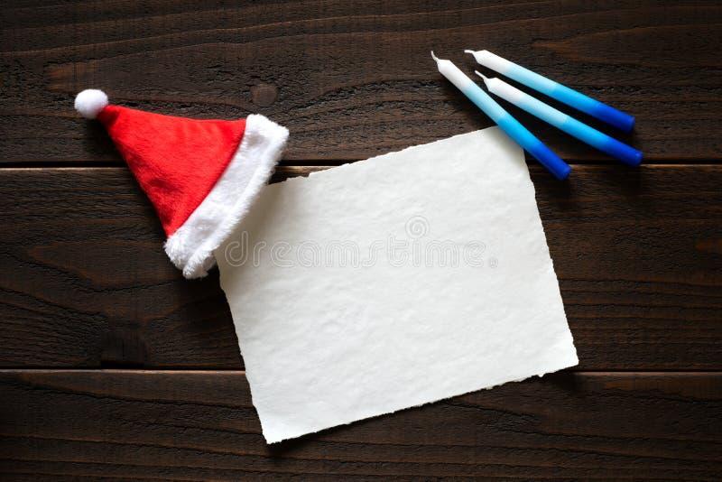 Boże Narodzenia lub Chrismukkah Wakacyjna Papierowa karta z Święty Mikołaj kapeluszem i Hanukkah świeczkami na Ciemnym Nieociosan obraz royalty free