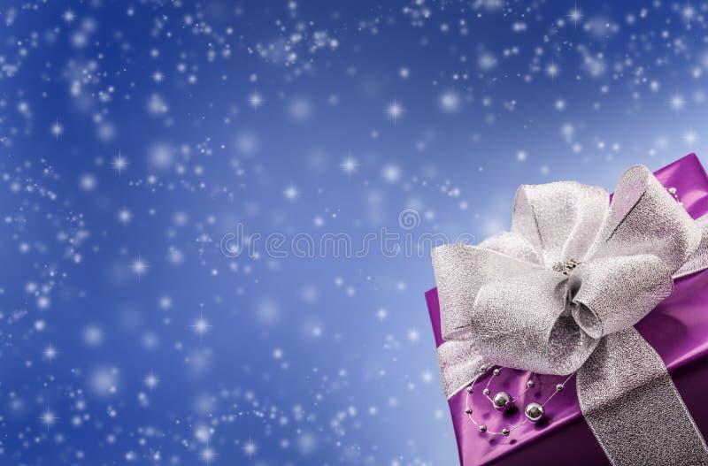 Boże Narodzenia lub walentynka purpurowy prezent z srebnym tasiemkowym abstrakcjonistycznym błękitnym tłem obraz royalty free
