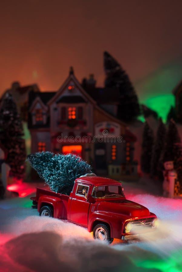 Boże Narodzenia miniaturyzują z Czerwoną rocznik ciężarówką dostarczają choinki na swój plecy zdjęcia stock