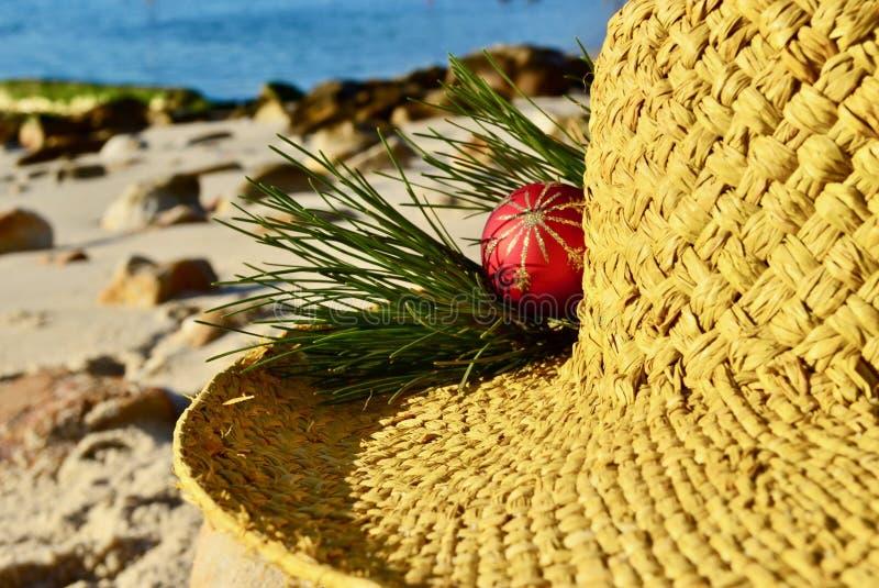 Boże Narodzenia morzem, czerwonej złocistej błyskotliwości Bożenarodzeniowa dekoracja na słomianym kapeluszu, boże narodzenia w L fotografia royalty free