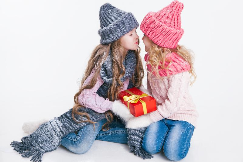 Boże Narodzenia nowy rok, Dwa małej siostry trzyma teraźniejszą w zimie odziewają Różowi i popielaci kapelusze i szaliki rodzina  zdjęcie royalty free