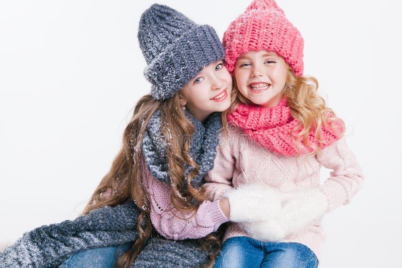 Boże Narodzenia nowy rok, Dwa małej siostry trzyma teraźniejszą w zimie odziewają Różowi i popielaci kapelusze i szaliki rodzina  obraz royalty free