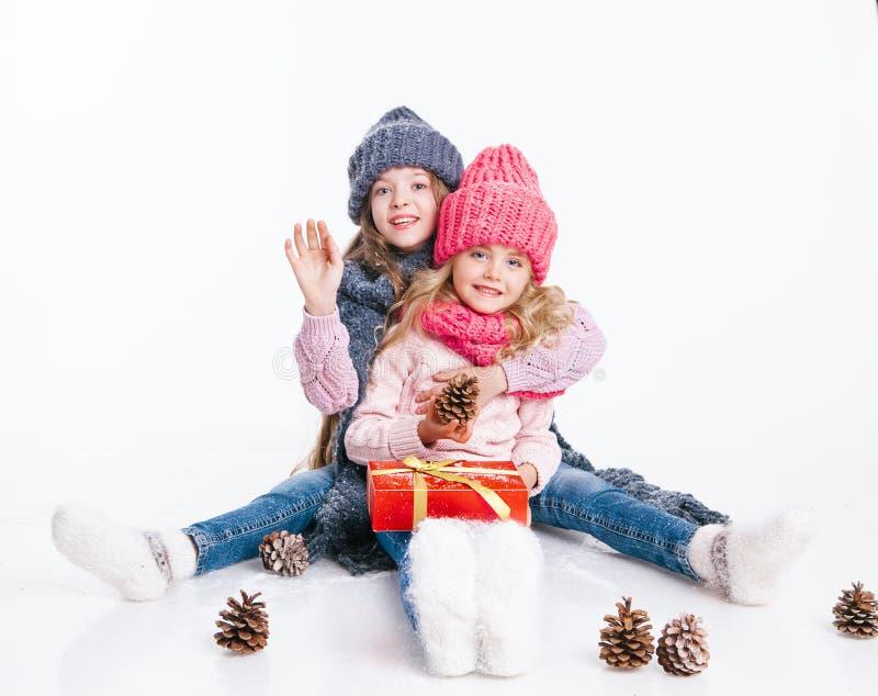 Boże Narodzenia nowy rok, Dwa małej siostry trzyma teraźniejszą w zimie odziewają Różowi i popielaci kapelusze i szaliki rodzina  obrazy royalty free