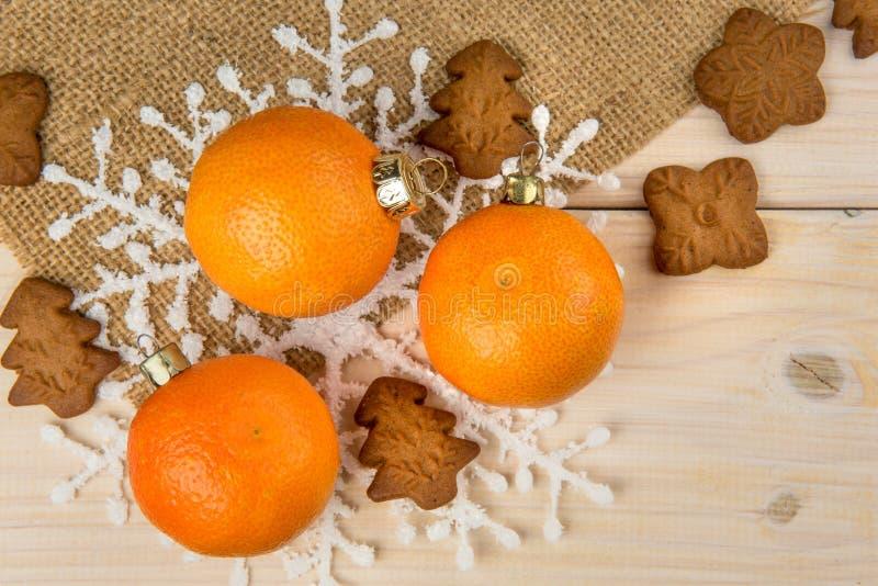 Boże Narodzenia, nowy rok tangerines lub piernikowi ciastka z płatek śniegu obramiającymi na brązie grabiją tło teksturę fotografia stock