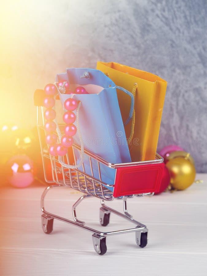 Boże Narodzenia pomijają pełno, Mały wózek na zakupy boże narodzenie prezenty, Robiący zakupy tramwaj z prezentów pudełkami zdjęcia stock