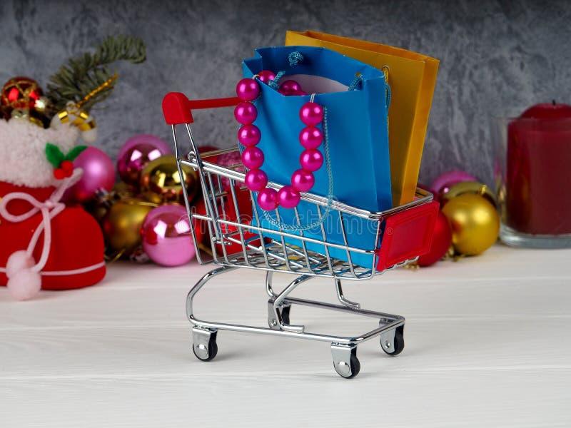 Boże Narodzenia pomijają pełno, Mały wózek na zakupy boże narodzenie prezenty, Robiący zakupy tramwaj z prezentów pudełkami fotografia stock