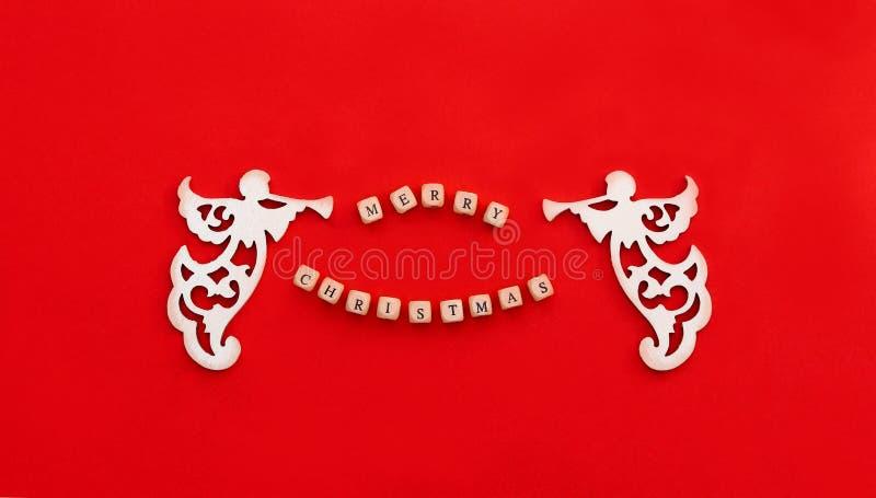 Boże Narodzenia rzeźbili drewnianych aniołów z trąbką i formułują Wesoło boże narodzenia na małych cegłach na czerwonym tle fotografia royalty free