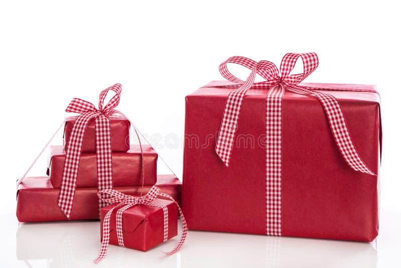 Boże Narodzenia: sterta czerwoni prezentów pudełka z łękiem i faborkiem, odizolowywająca obrazy royalty free