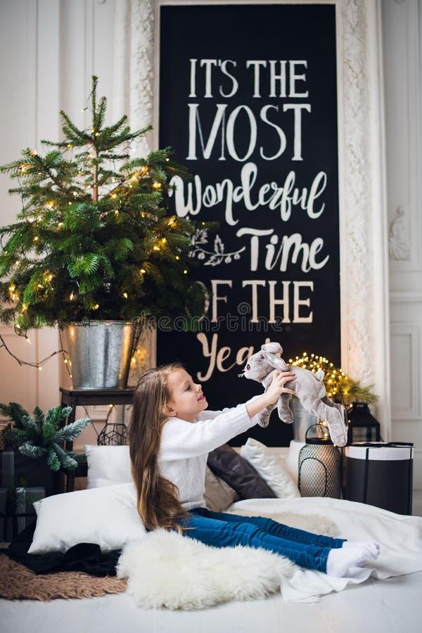 Boże Narodzenia stwarzają ognisko domowe dekorację Troszkę dziewczyny dziewczyny obsiadanie na szkockiej kracie na podłoga Bardzo obraz stock