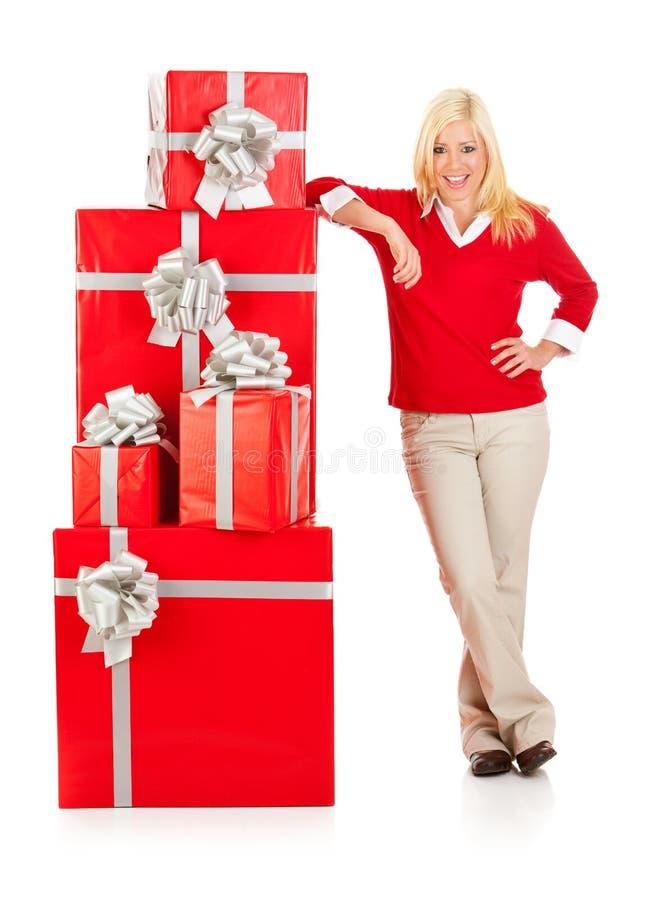 Boże Narodzenia: Uśmiechnięta kobieta Opiera Na stercie Czerwoni Bożenarodzeniowi prezenty obraz stock