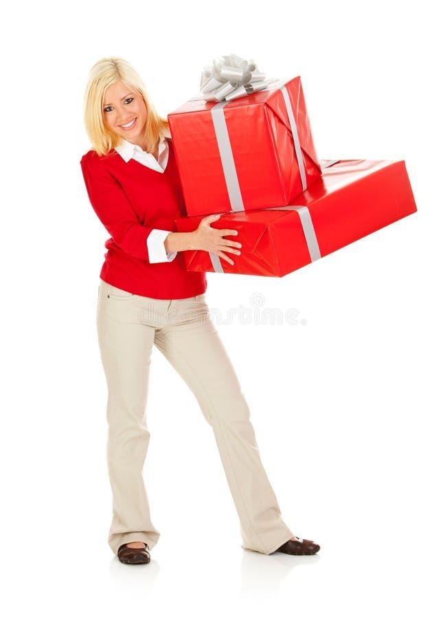 Boże Narodzenia: Uśmiechnięta kobieta Podtrzymywał stertę Bożenarodzeniowi prezenty obrazy royalty free