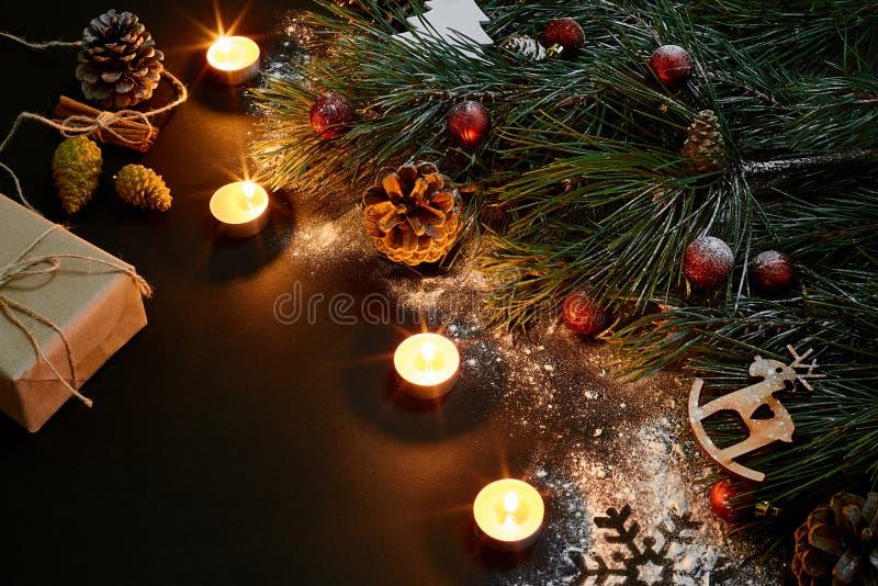 Boże Narodzenia Xmas zabawki, płonące świeczki i świerczyna, rozgałęziają się na czarnego tła odgórnym widoku Przestrzeń dla teks obrazy stock
