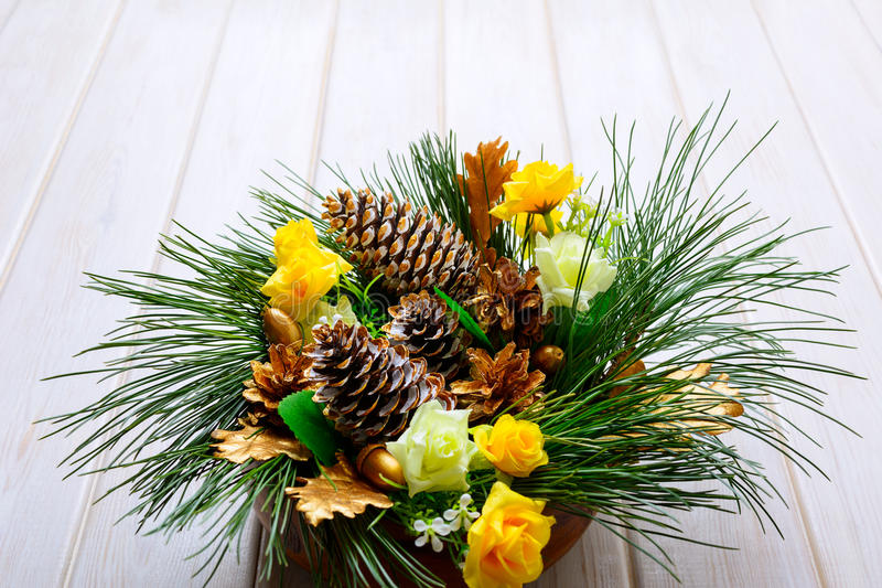 Boże Narodzenia zgłaszają centerpiece z złotymi sosnowymi rożkami i jedlinowym branc zdjęcie royalty free