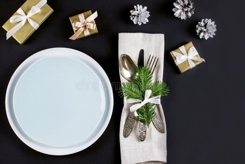 Boże Narodzenia zgłaszają położenie z talerzami, silverware, prezenta pudełkiem i dekoracjami w, czerni i złoto kolorach fotografia royalty free
