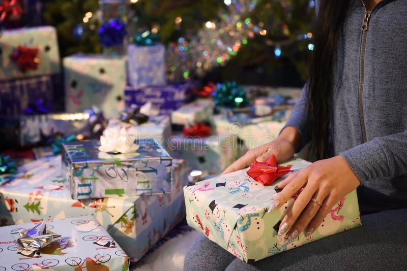 Boże Narodzenie pakunki z prezentami w rękach dziewczyna obok choinki i mnóstwo pudełek z nowego roku ` s bożych narodzeń gif zdjęcia stock