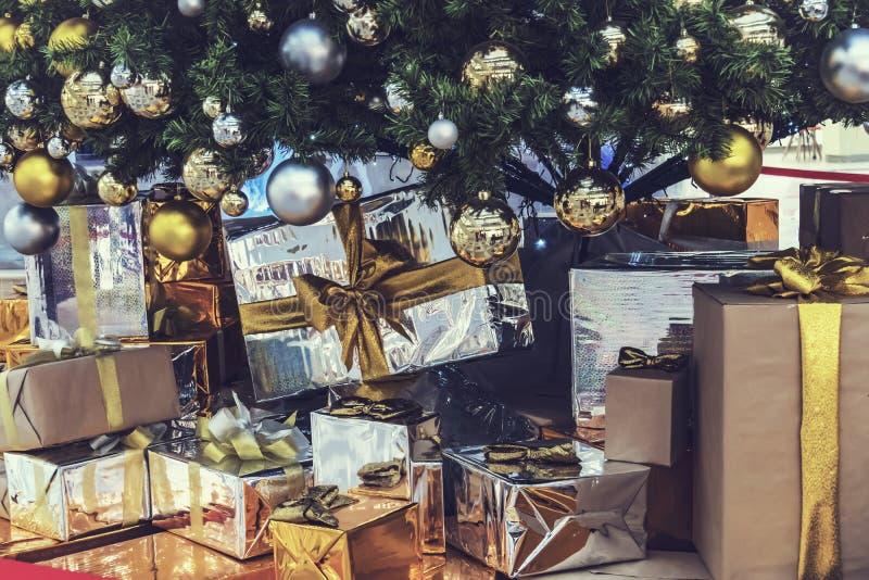 Boże Narodzenie pakunki z prezentami w rękach dziewczyna obok choinki i mnóstwo pudełek z nowy rok Bożenarodzeniowymi prezentami fotografia royalty free