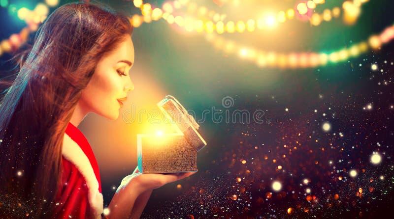 boże narodzenie w tle obramiająca wakacyjna scena Piękno brunetki młoda kobieta w partyjnym kostiumowym otwarcie prezenta pudełku zdjęcie royalty free