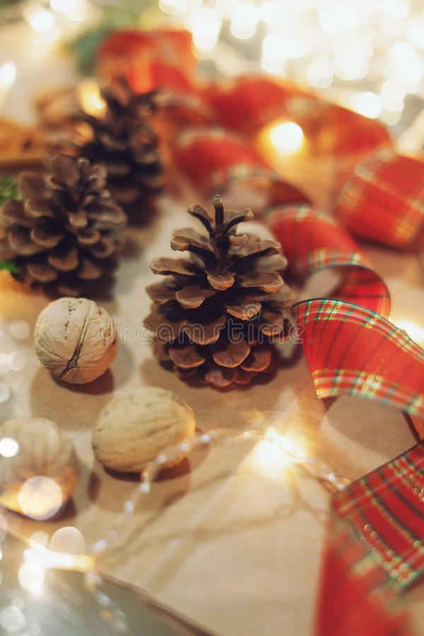 Bożego Narodzenia szyszki, czerwona wstążka i świąteczne światła obraz royalty free
