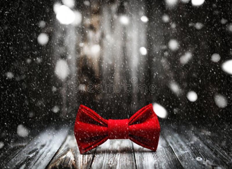 Bożenarodzeniowa łęku krawata dekoracja z śniegiem na białym drewnianym tle Wakacyjny Chrismas pocztówki ramy projekt z kopią fotografia royalty free