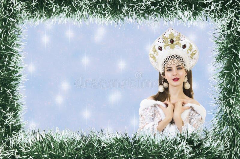 Bożenarodzeniowa boże narodzenie karta z piękną, młodą, uśmiechniętą kobietą ubierającą jako Święty Mikołaj, graniczący sosnowymi fotografia royalty free
