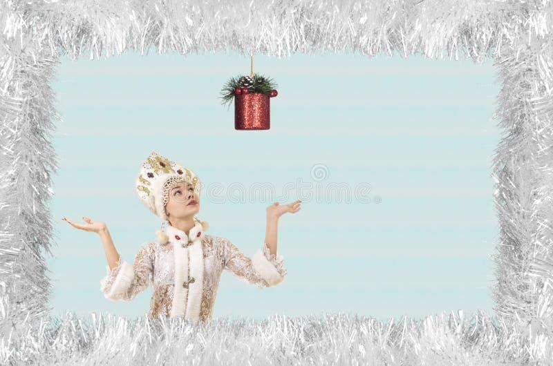 Bożenarodzeniowa boże narodzenie karta z piękną, młodą, uśmiechniętą kobietą ubierającą jako Święty Mikołaj, graniczący sosnowymi obraz royalty free