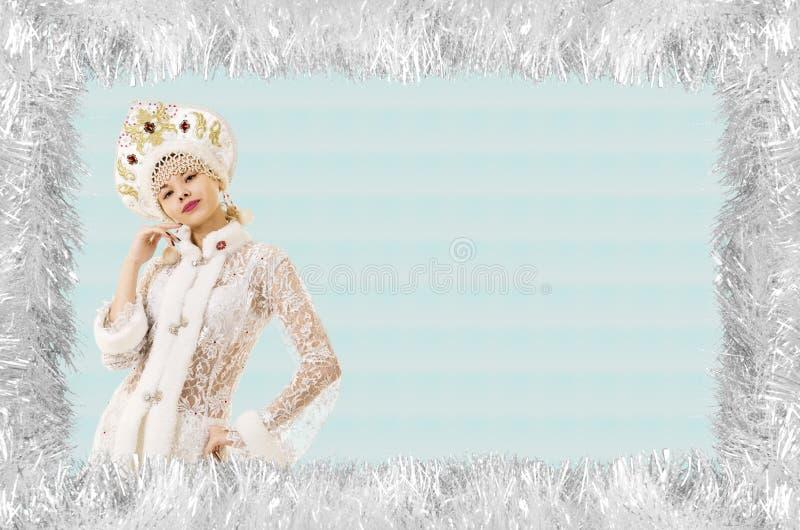 Bożenarodzeniowa boże narodzenie karta z piękną, młodą, uśmiechniętą kobietą ubierającą jako Święty Mikołaj, graniczący sosnowymi zdjęcia stock