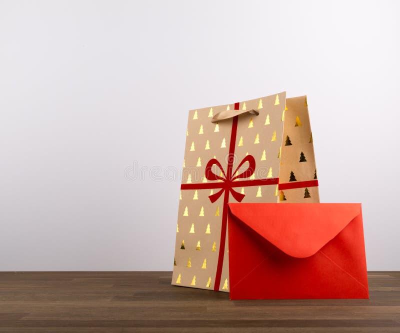 Bożenarodzeniowa Brown Papierowa torba z faborkiem i Czerwona koperta na drewnianym stole odizolowywającym na białym tle obrazy stock