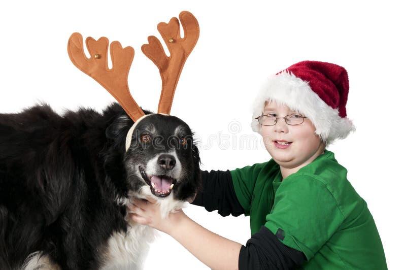 Bożenarodzeniowa chłopiec i jego reniferowy pies fotografia royalty free