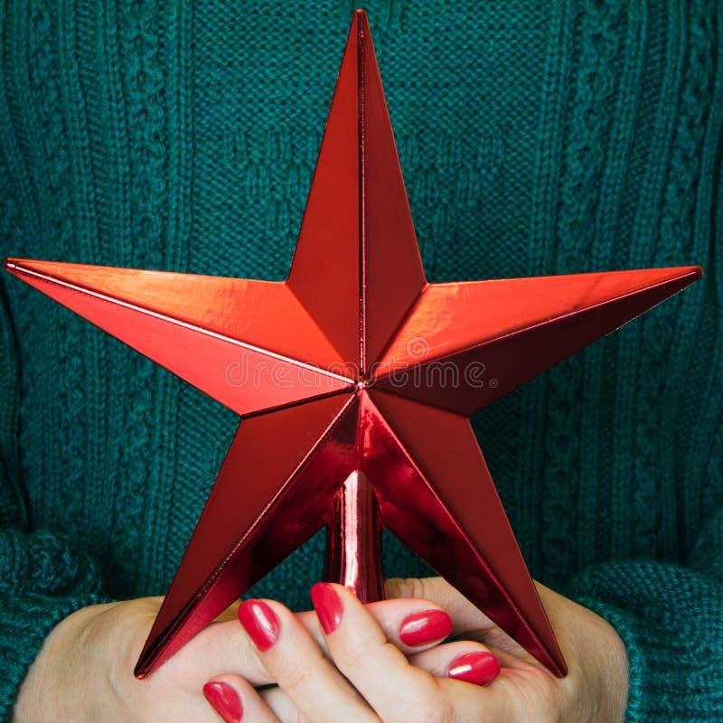 Bożenarodzeniowa czerwieni gwiazda dla wierzchołków chistmas drzewnych w kobiety ręce joyce Wystrój dla Cristmas drzewa zdjęcia royalty free