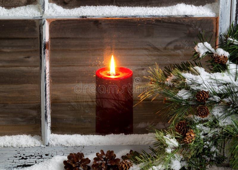 Bożenarodzeniowa czerwona świeczka z śniegiem zakrywał domowego okno i sosny obraz royalty free