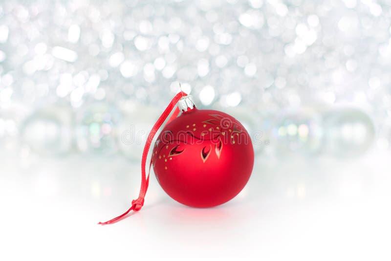 Bożenarodzeniowa czerwona piłka na czerwonym faborku na tle błyszczący świecidełko, biali bolls, światła i błyska bokeh zakończen obraz stock