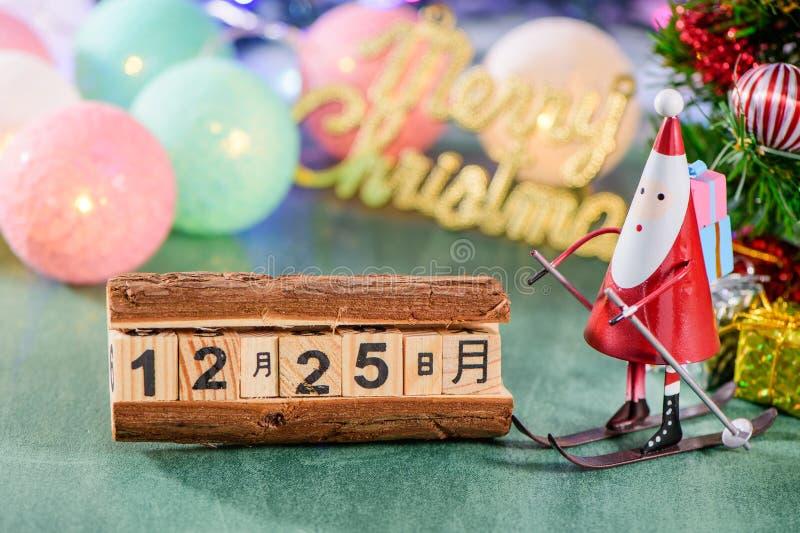 Bożenarodzeniowa dekoracja, łyżwiarski Santa Claus z Bożenarodzeniowy metaforyka przy Grudniem 25 odizolowywającym na zielonym tl zdjęcia royalty free