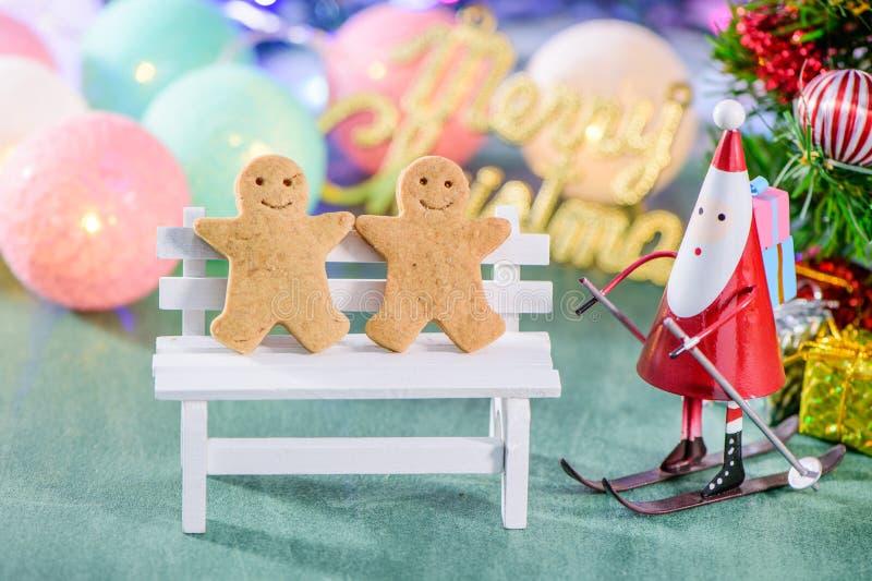 Bożenarodzeniowa dekoracja, łyżwiarski Santa Claus z metaforyka odizolowywający na zielonym tle, piernikowego mężczyzna i bożych  zdjęcia stock
