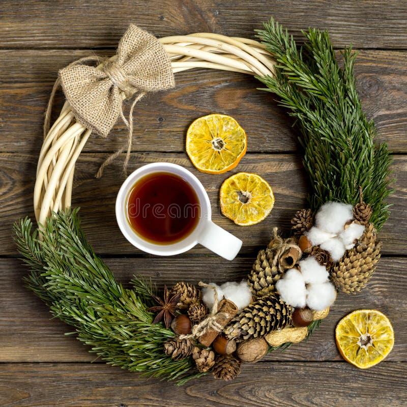 Bożenarodzeniowa dekoracja, Bożenarodzeniowy wianek, choinek gałąź i filiżanka herbata na rocznika drewna teksturze, fotografia stock