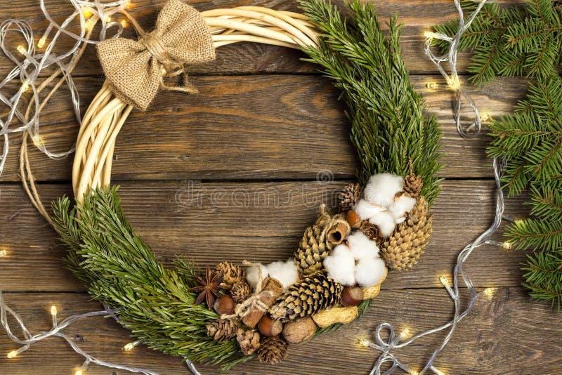 Bożenarodzeniowa dekoracja, Bożenarodzeniowy wianek, choinek gałąź i girland światła na rocznika drewna teksturze, zdjęcie stock