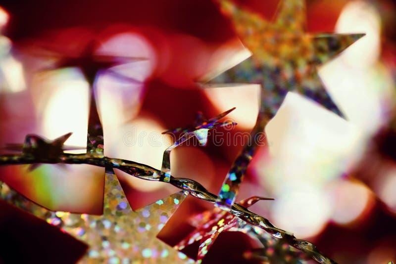 Bożenarodzeniowa dekoracja, wibrujące złote gwiazdy, srebro łańcuch i bokeh, zdjęcie royalty free