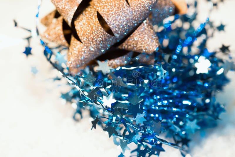 Bożenarodzeniowa dekoracja z błękita łańcuchem z gwiazdami i złotym łękiem obraz stock