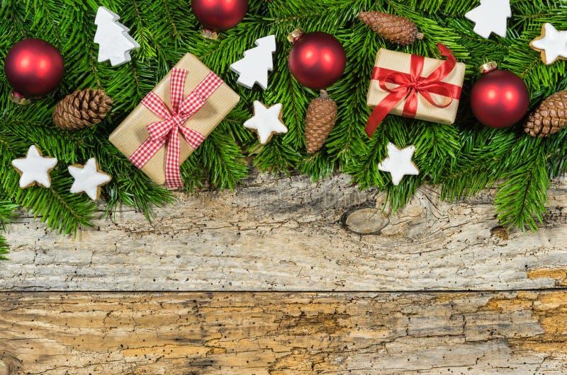 Bożenarodzeniowa dekoracja z prezentami, czerwonymi piłkami, jodły zieleni ramą i ornamentami na drewnianym tle, zdjęcia stock