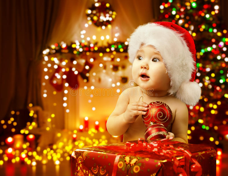 Bożenarodzeniowa dziecka otwarcia teraźniejszość, Szczęśliwy dzieciaka Santa kapelusz, Xmas prezent zdjęcia royalty free