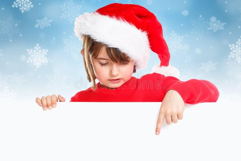 Bożenarodzeniowa dziecko dzieciaka dziewczyna Święty Mikołaj wskazuje pustego sztandaru śnieg zdjęcie royalty free