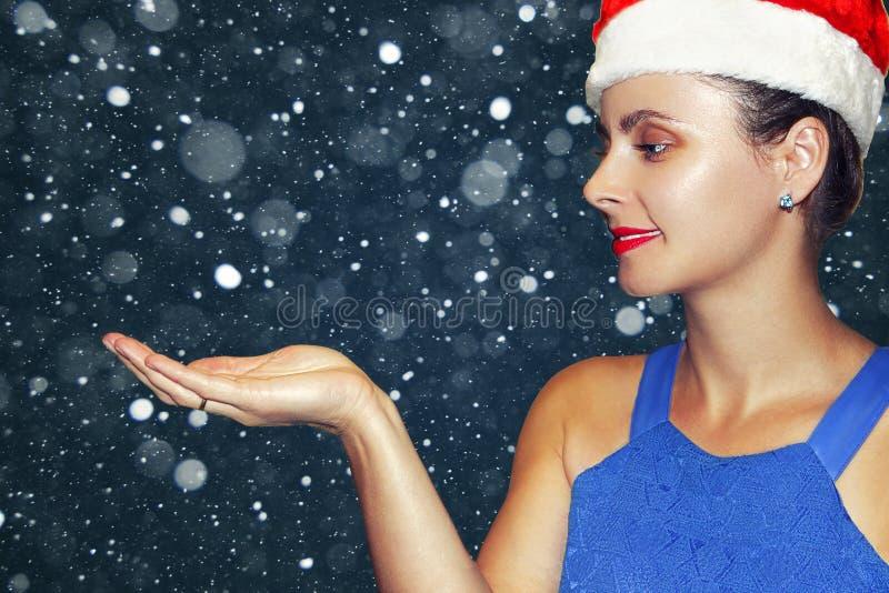 Bożenarodzeniowa dziewczyna w Święty Mikołaj kapeluszu na opadu śniegu tle Piękno mody model łapie płatki śniegu w palmie ręka Xm zdjęcia royalty free