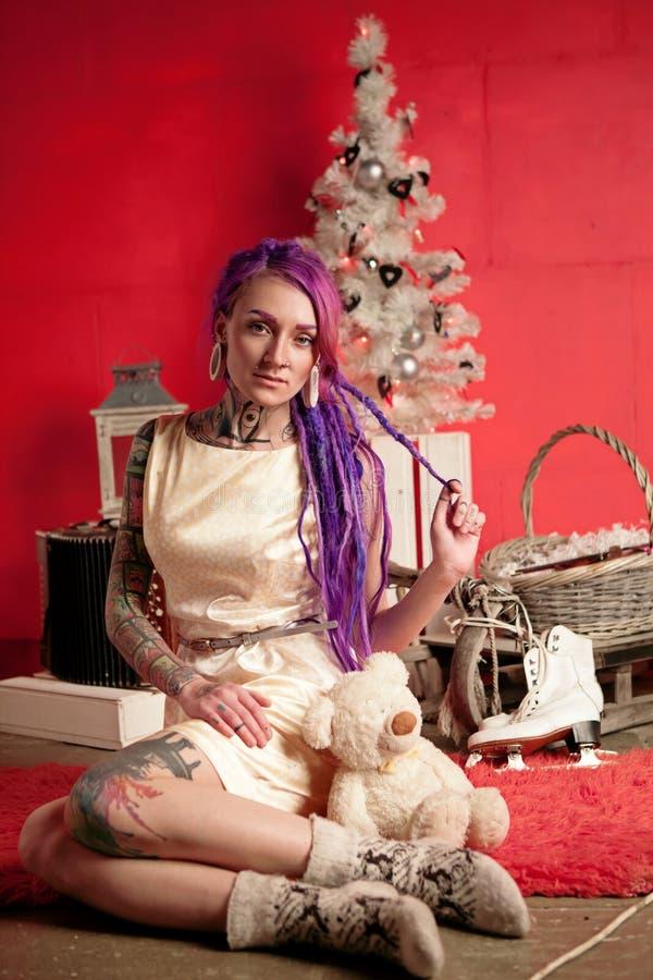 Bożenarodzeniowa fotografia dziewczyna z purpurowymi dreadlocks i tatuażami w studiu zdjęcia royalty free