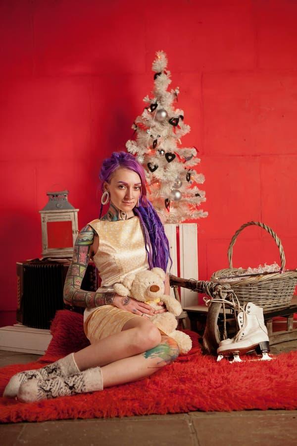 Bożenarodzeniowa fotografia dziewczyna z purpurowymi dreadlocks i tatuażami w studiu obraz royalty free