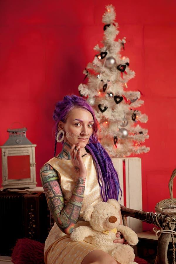 Bożenarodzeniowa fotografia dziewczyna z purpurowymi dreadlocks i tatuażami w studiu zdjęcie royalty free